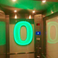 Zeleně svítící číslovka 0 jako informační značení nultého patra ve výtahu, skleněné stěny výtahu, ovládací panel