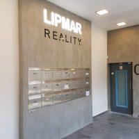 Vstupní místnost, interiér, na bílé stěně umístěný šedý panel, nahoře uprostřed bílý nápis LIPMAR, pod ním černý nápis REALITY, pod nimi 21 schránek, vpravo šedá stěna a černé dveře