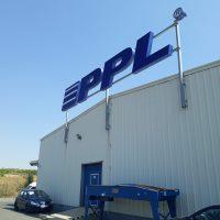 Budova s bílým pláštěm, nad ní na tyčích umístěné modré mohutné logo PPL, v popředí dvě modrá auta, uprostřed budovy modré dveře, modrá obloha v pozadí