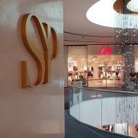 3D zlaté logo tvaru propojených velkých tiskacích písmen SP umístěné na světlou stěnu v prostředí obchodního domu