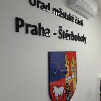 Černý 3D nápis Úřad městské části Praha - Štěrboholy níže doplněný barevným erbem přilepený na bílou zeď, pod klimatizační jednotku