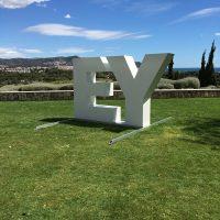 Dvě velká bílá 3D písmena E a Y, umístěná v exteriéru na trávě, v pozadí město, krajina a modrá obloha