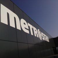 Detailněji vyfocené bílé logo firmy metrostav přilepené na černém plášti budovy v pozadí s modrou oblohou.