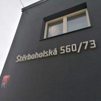 Bílý 3D nápis, označuje číslo budovy a název ulice, přilepený na černou fasádu budovy pod bíle rámovaným oknem.