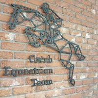 Černé geometrické logo ve tvaru jezdce na koni doplněné o černý nápis Czech Equestrian Team připevněné na cihlovou zeď v blízkosti černých otevřených dveří