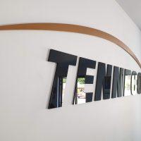 3D černý nápis TENNECO laserem vyřezaný z plexiskla doplněný o lakovaný oblouk hnědozlaté barvy nad ním. Celé logo je nalepené na bíle zdi v interiéru.