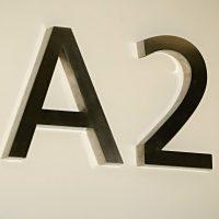 3D písmena A2 vyfrézovaná ze stříbrného hliníku s plechovými boky, připevněné distančními trny na bílé zdi