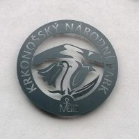 Kulaté hliníkové logo Krkonošského národního parku připevněné na bílou fasádu.