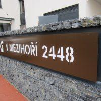 Hnědá poutací tabule s malým bílým logem v levé části a bílým nápisem V MEZIHOŘÍ 2448, připevněná na kamennou pomřížovanou stěnu.
