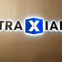 Černý bíle podsvícený nápis TRAXIAL a pod ním napravo malý nápis Traxial group, písmeno x je bílé a vyražené do modrého šestiúhelníku, vše umístěné na bílé stěně