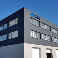 Modré logo ve tvaru lotusového květu doplněné tmavě modrým logem vpravo, přilepené na plášt šedé obdélníkové budovy s pásovými okny v pozadí s modrou oblohou