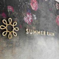 Zlaté 3D logo ve tvaru Slunce a 3D nápis SUMMER RAIN zlaté barvy připevněné na hnědou žíhanou interiérovou stěnu s potiskem květin v horní části.