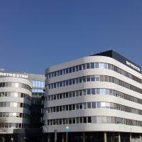 Šedobílá budova s pásovými okny a zaoblenými rohy, vzadu s černou částí budovy s černým pláštěm a velkými bílými logy firmy Metrostav v pravé i levé části budovy, v pozadí modrá obloha.