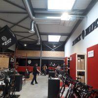 Černé mohutné logo firmy ZEUS BIKE umístěné na bílé stěně, která plynule navazuje na červenou stěnu níže, v prodejně kol.