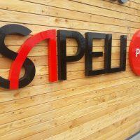 3D černo-červené logo firmy SAPELI s 3D červeným kruhem s bílým nápisem point na pravé straně, přilepené na dřevěný obklad budovy.