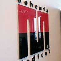 3D červenočerné logo ve tvaru písmena M z podbarveného plexiskla doplněné nahoře o černý 3D nápis Bohemia a dole Medical, přilepené na bílé zdi.