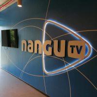 Modrá interiérová stěna s bílými geometrickými čarami, uprostřed stěny bílé logo nangu tv, gu a tv je v zaobleném bílém trojúhelníku, který je bíle podsvícený, nalevo na stěně černá televize, dole šedá podlaha, nalevo v pozadí bíle osvícený exteriér