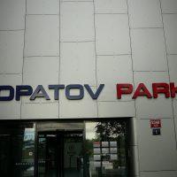 Velké modro/červené matné logo zhotovené z extrudovaného polystyrenu a polepené nastříkaným plexisklem, přichycené na šedé fasádě budovy nad vstupními dveřmi.
