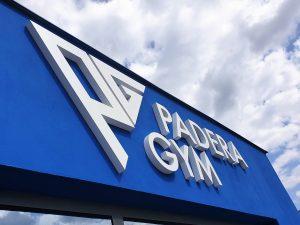 Bílý 3D nápis a logo Padera Gym na modré fasádě budovy