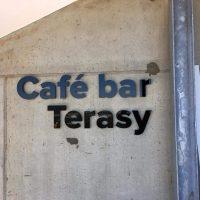 Černomodrý 3D nápis café bar Terasy umístěný na šedou betonovou stěnu.