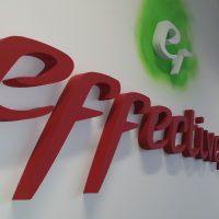 Mohutný 3D červený nápis effective nahoře doplněný o bílé 3D logo tvaru e na světle zeleném nepravidelně kruhovém podkladu, umístěno na bílé stěně v interiéru