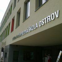 Stříbrný nápis velkými tiskacími písmeny STŘEDNÍ PRŮMYSLOVÁ ŠKOLA OSTROV připevněný na světlou fasádu budovy těsně nad převis nad vchodem školy