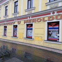 Žlutý dům s klasicistní fasádou, dvě řady oken, dolní řada oken potištěná reklamami, nad okny nápis POTRAVINY U HEROLDŮ, oranžový, nad tím přerušovaná červená čára na bílém podkladu přes celý dům, v popředí stojan na kola a asfalt