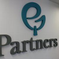 Šedý 3D nápis Partners výše doplněný oblým tyrkysovým logem umístěný na bílé stěně v interiéru