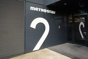 Označení budovy částí číslice 2 z bílého dibondu na černém plášti budovy, bílé logo Metrostav, odraz ve skleněných dveřích za čistící zónou