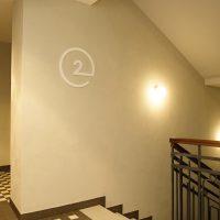 Bílá 3D číslice 2 v kružnici na stěně jako označení druhého patra