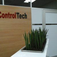 Sukulentní rostlina tvaru jednotlivých stojících trnů zasazená do bílého nábytkového kvádru v pozadí s dřevěnou stěnou a červeno-černým nápisem ControlTech a bílými dveřmi vpravo
