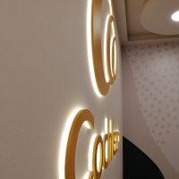 Detailně vyfocený 3D nápis/logo na bílé stěně, podsvícené bílým světlem, v pozadí nahoře světlo