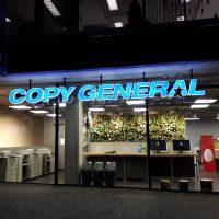 Prodejna z exteriéru, v popředí chodník, prosklené stěny, v horní části led podsvícený nápis COPY GENERAL modré barvy s bílými obrysy, uvnitř prodejny elektronická zařízení