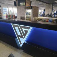 Barový pult modré barvy s černou deskou nahoře a černým bannerem dole, uprostřed světlé světelné logo tvaru obráceného trojúhelníku s šedými písmeny p a g, v prostředí fitness centra