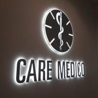 Tmavě šedý nápis CARE MEDICO a nad ním kulaté logo, podsvíceno bílým světlem, umístěno na světlé stěně