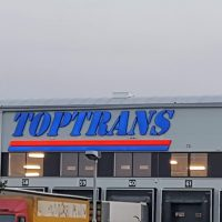 Horní část bílé skladové budovy, dole několik vstupních bran pro nakládku kamionů, v popředí několik kamionů, nahoře modré logo TOPTRANS, podtržené červenou a modrou linkou