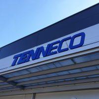 Detailněji vyfocené prosklené přední zastřešení budovy, na světlé přední desce modrý nápis TENNECO, nahoře pokračuje modrá budova