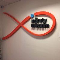 Oranžové 3D logo tvaru ryby s modrým 3D puntíkem v horní části a černým 3D nápisem infinity telecom uprostřed. Umístěno na bílou stěnu v interiéru.
