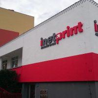 Velké šedočervené logo inetprint s malým šedým nápisem v dolní levé části, přilepené na pravé části bílo-čevené budovy v blízkosti panelových domů.