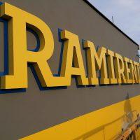 3D žlutý nápis RAMIRENT přišroubovaný na šedý plášť budovy, kolem nápisu modré obrysy. Vpravo kus montážního stroje, montér a okolí budovy.