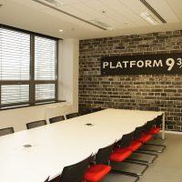 Fototapeta s motivem zdi a cedulí PLATFORM 9 3/4 nalepená na stěně zasedací místnosti, bílý konferenční stůl, černo-červené židle, okno s roletami