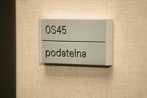 Dveřní štítek s gravírovaným černým textem podatelna a označením místnosti OS45, hliníkové lišty, béžová textilní tapeta