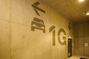 Šedý malovaný nápis na betonové zdi, šipka vlevo, šipka dolů, piktogram auta a jízdního kola, číslice 1 a písmeno G, prosklené dveře s černým rámem