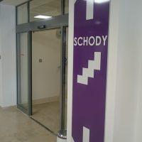 Fialový informační panel s šipkami nahoru a dolů, označením SCHODY, nalepený na bílé zdi vedle skleněných dveří