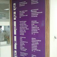Fialový orientační panel POLIKLINIKY PROSEK s bílým 3D značením pater, nalepeno na zdi chodby