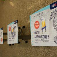 Čtyři reklamní tabule na kolečkách potištěné barevnou samolepicí folií, reklamy společnosti PRE MOBIL na chodbě