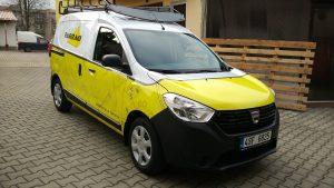 Auto Dacia Dokker polepené folií, spodní část žlutá s motivem technického výkresu, kabina a nástavba bílá, na zemi zámková dlažba