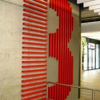 Řady svislých a vodorovných červených hranolů ve tvaru písmene B nalepené na zdi, označení budovy, nerezové zábradlí