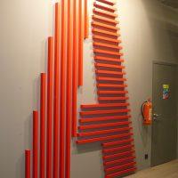 Řady svislých a vodorovných červených hranolů ve tvaru písmene A na šedé zdi, označení budovy, hasící přístroj, kovové dveře