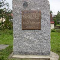 Bronzová litá deska ve tvaru čtverce s 3D informačním textem, přimontovaná na kamenné desce, kolem trávník, v pozadí stromy